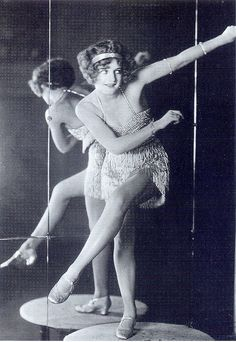 "From the book: ""World champion Charleston dancer Bee Jackson wears a beaded and fringed dance dress, popular at the time, as the fringes would shimmer and shake and draw attention to movement. This dress is shorter than the typical styles of the era. Paste jewellery known as ""slave bracelets"" was often worn high up on the arm as well as the wrist.""    Scanned from ""Decades of Fashion"" by Harriet Worsley."