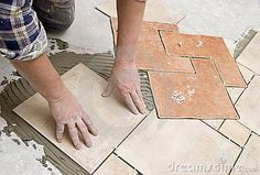 A construction worker putting on new floor tiles.  <a href='http://www.dreamstime.com/interiors-rcollection5192-resi208938' STYLE='font-size:13px; text-decoration: blink; color:#FF0000'><b>HOME BUILDING & RENOVATION »</b></a>