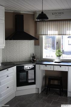 valkoinen keittiö,valkoinen välitila laatta,valkoinen peiliovi,keittiö,petra-keittiö,harmaa kaakelilattia,induktioliesi,musta liesituuletin,keittiönkaapit,keittiön välitila