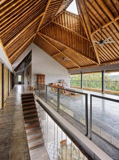 The house's roof features a bamboo structure which is exposed internally, adding warmth and a natural detail to the upper-floor living spaces.