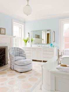 Blue and white is a classic pairing. A whimsical tile pattern on the floor, a cozy uphlolstered chair, and a stately fireplace elevate the basic palette in this master suite to create a relaxing retreat.