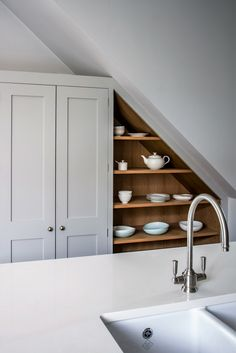Sustainable Kitchens - Rockhouse Barn. A beautiful oak shaker style double larder painted in Farrow & Ball Pavilion Gray sits next to bespoke under-stair cabinetry which displays ceramics. Also visible is the Bianco Puro worktop on the centre island with a Shaws classic double sink and Abode Hargrave Brushed Nickel tap.