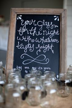 a pretty chalkboard is placed next to the drinks at a reception - thereddirtbride.com - see more of this wedding here