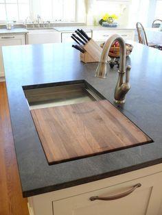 Cutting board built into sinktop, trash can under chopping board location.
