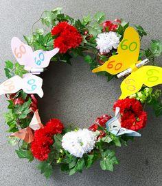 Kranz mit Efeu umwickelt. Blumen einstecken und Schmetterlinge aus Geldscheinen falten. Weitere Schmetterlinge aus verschiedenen farbigen Tonkarton ausschneiden. Und am Kranz befestigen.