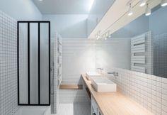 Minimalista e funzionale, il bagno è rivestito da piastrelle quadrate bianche. Il mobile del doppio lavandino è in legno di rovere ed è stato disegnato su misura dai progettisti di Septembre