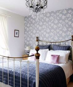 This gray floral paper looks shabby-chic behind a wrought-iron bed!