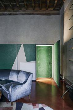 La maison de Roberto Baciocchi en Toscane Dans la Salle à manger, le long placard, peint par un ami, dissimule une porte. Le canapé vintage est recouvert de velours bleu gris et le tapis date des années 1980.