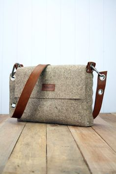 Mens felt satchel bag which is handmade from 3 mm industrial wool felt, which is assembled using pop rivets. The strap is made from 100% vegetable tanned