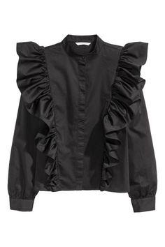 フリルブラウス: コットン織物素材のブラウス。小さなスタンドカラー。フロントボタンが隠れる比翼仕立て。ゆるやかなドロップショルダー。ややゆったりした長袖で、ボタン留めのカフス付き。大きなフリルがフロントからバックの途中までつながったデザイン。
