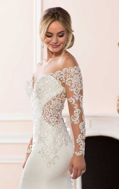 Sexy and chic in every single way, this long sleeve off-the-shoulder wedding dress by designer Stella York is one of a kind! Lace and crepe create a very sexy sheath silhouette with deep, sheer side cutouts and lacy long sleeves that fall gently off the shoulders. Richly-beaded lace covers the bodice with strong silver details made of bugle beads, pearls and sparkling Diamante beads. A flared crepe skirt is finished in laser-cut lace for added drama. A low back with deep, sheer side cutouts…