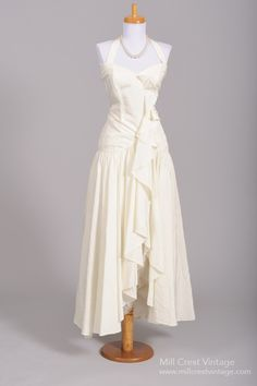Designed in the 80's, this fabulous vintage wedding dress is done in a French vanilla toned rayon over an acetate lining in the bodice.  The bodice features ...