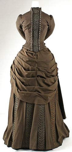 Ensemble Designer: Redfern (1847–1940) Date: 1887–89 Culture: French Medium: wool, silk, cotton, metallic thread Dimensions: Length at CF (a) neckline to point): 21 in. (53.3 cm) Length at CF (a) neckline to waistline): 15 x 28 x 56 in. (38.1 x 71.1 x 142.2 cm) Length at CF (b): 42 x 42 x 22 1/2 x 140 in. (106.7 x 106.7 x 57.2 x 355.6 cm) Width (d): 8 1/2 x 7 in. (21.6 x 17.8 cm) Credit Line: Gift of Orme Wilson and R. Thornton Wilson, in memory of their mother, Mrs. Caroline Schermerhorn…