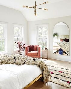 Add pops of color to a white, neutral bedroom by adding an accent arm chair and bright textiles, such as a throw or rug