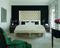 Dramatic tufted headboard against one inky black accent wall. yums. campaign nightstands?