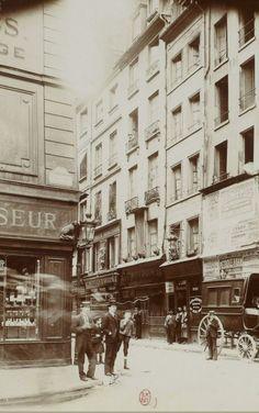 Du coin de la rue de La Reynie et de la rue Saint-Denis, vers 1900, on voit au n° 33 la célèbre pharmacie d'époque 'Au Mortier d'Argent'. Une photo de la collection Georges Sirot - Bibliothèque Nationale  (Paris 1er)