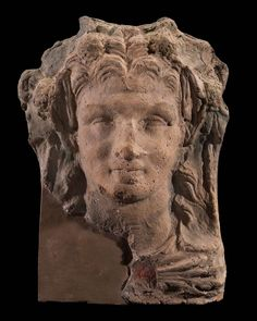 Head of satyr. Long hair, pointed ears, garland of ivy leaves and berries. Uniform gray color; vestiges of green in the garland. Handle behind. A large piece broken away at the left below.ETRUSCAN,ROMAN PERIDOD