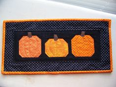 "Sew Lux Fabric : Blog: Pumpkin Block Tutorial...posted by Chrissy...I did some free motion quilting to make the pumpkin look a little more round.  I think it at least gives the illusion of roundness.  :-)  This mini is about 8"" x 17"".Start with one 4"" square of an orange print.  I used Essential Dots in Orange. You'll also need four 1.5"" squares in black solid.  I used Bella Black."