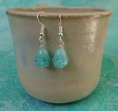 These simple earrings have been made with beautiful, glass lamp work beads in a drop shape. They have a cool mint base with a raised decoration in teal, white and aqua. The ear wires are silver plated. They have a drop of just over half an inch. Simple Earrings, Bead Earrings, Silver Earrings, Handmade Jewellery, Earrings Handmade, Organza Gift Bags, Silver Plate, Glass Beads, Teal