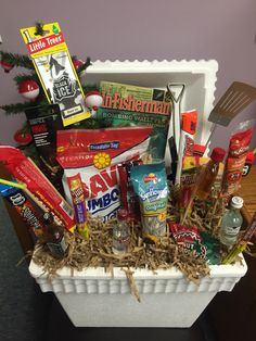A great idea for the outdoorsman! Styrofoam cooler fishing magazine potato chips meat sticks candy bars sunflower seeds mini liquor bottles grilling utensils fishing bobbers And assorted tackle. Diy Father's Day Gift Baskets, Liquor Gift Baskets, Diy Christmas Baskets, Fathers Day Gift Basket, Diy Father's Day Gifts, Christmas Gift For Dad, Father's Day Diy, Raffle Baskets, Fathers Day Gifts Fishing