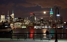 A full moon rises behind the Empire State Building in New York as a man watches in a park along the Hudson River in Hoboken, New Jersey  Picture: REUTERS/Gary Hershorn