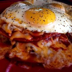 Huevos Rancheros with Lightly Crisp Corn Tortillas in Spicy Enchilada Sauce with Refried Black Beans, Soy Chorizo and Melted Cheddar Jack Cheese topped with Sunny-Side Up Eggs