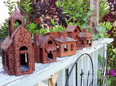 Rusted tin old town buildings on the peeling painted wooden ledge in green garden. DJ Laughlin Art Photograph
