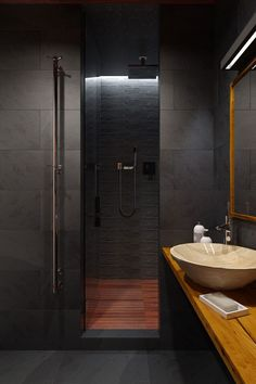 Shower area of the small bathroom inside the stylish bachlor loft clad in slate and teak