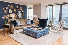 Sitting behind a taupe velvet sofa in this living room is a starburst mirror collage positioned on a navy accent wall. Designer SuzAnn Kletzien also reupholstered an egg chair in a navy velvet fabric and had a custom ottoman made with a removable tray in the center. Glass doors provide access to the condo's balcony area.