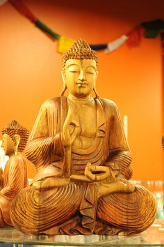 """Carved Buddha statue in wood, slight smile, eyes closed, detailed robes, orange wall, prayer flags, store,   Anchorage, Alaska, USA      """"Do not look for approval except for the consciousness of doing your best."""" -Andrew Carnegie"""