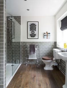 bathroom with gray subway tile walls, pantone sharkskin used in interior design, warm brown wood floor, frameless glass shower enclosure, vintage bathroom design