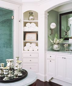 Mercury-glass vases are arranged on a marble-topped antique table in the master bath. The bath features a marble-walled shower with a glass door and his-and-her vanities in wood-trimmed niches.