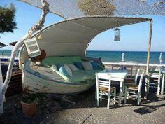 boat turned into a cute seating area! great for a beach, but could be nice by a pond too