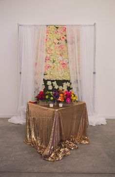 Sweetheart table decorated with a gold sequin tablecloth, colorful flowers and a floral backdrop| A Bright & Colorful Mexican Glam Themed Wedding|Photographer: Ann Axon Photography