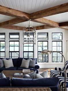 Coastal, preppy living room with navy and striped couches, metal arc lamp, exposed beams and white walls   Muskoka Living