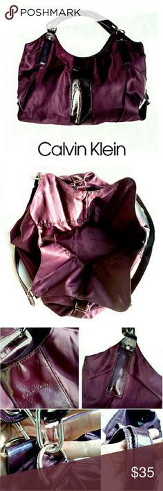 "CALVIN KLEIN FALL COLOR PLUM HOBO BAG CALVIN KLEIN PLUM COLOR HOBO BAG THIS IS THE FALL COLOR THIS YEAR PLUM! Pre-Loved  Beautiful PLUM Color Nylon & ""patent leather"" Straps & Accents with Silver Tone Metal Hardware. Spacious Lined Clean Interior w/Magnetic Closure.  Some Minor Wear on Handles (pic 4)  Approx Meas; Drop 12"" H 14"" W 18""  Pls See All Pics. Ask ? If Needed Calvin Klein Bags Hobos"