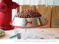 """jessica had a great idea to make a cake that resembled """"dog chow."""" she cooked the cake in a glass bowl, then turned it upside down, frosted it, then added coco puffs and put in in a real dog dish she got at the pet store! brillant!"""