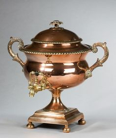 A Regency Period Copper Samovar - c. 1815 - An ornate Regency period copper samovar; of trophy form; with vented cover with a flower finial and scrolling acanthus leaf handles. The spigot with turned ebony handle; with a waisted stem raised on bun feet..