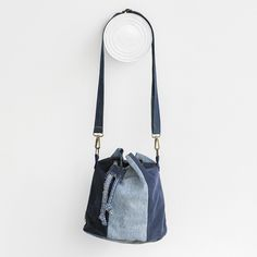 Oval-shaped bucket bundle. Strips Texan adjustable and fastened by carabiners. Perimeter adjustment with denim strip. Interior denim and lining pocket