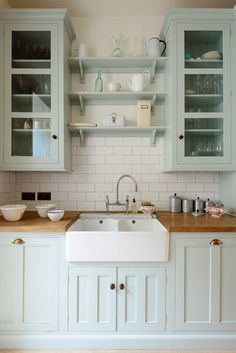 Palest blue kitchen cabinets topped with an apron sink and butcher block counters.