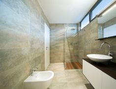 """Simulate a Spa: """"large-format tile connects the floor to the walls."""" I also like the solid, unmoving glass shower wall."""