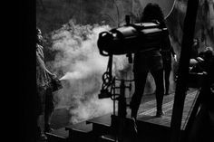 Two members of stage crew fill the stage with smoke, creating Violetta's atmospheric opium den.