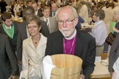 "Lutheran World Federation (LWF) President Bishop Mark. S. Hanson, holding a pine foot-washing tub, leads participants from the plenary hall to the Alte Reithalle for a ""Service of Repentance"" — a special church service that followed the historic July 22, 2010, reconciliation action between Anabaptists and Lutherans at the Eleventh LWF Assembly in Stuttgart, Germany. Janet Plenert, executive secretary (Witness), Mennonite Church Canada, and vice president of the Mennonite World Conference…"