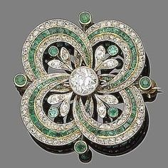 An emerald and diamond brooch/pendant, ca 1915. Centrally-set with an old brilliant-cut diamond within an openwork quatrefoil set with alternating rows of calibré-cut emeralds and rose-cut diamonds, accented with circular-cut emerald and single-cut diamond flowers, principal diamond approx. 0.85ct, by amelia