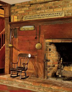 An antique child's chair accentuates the size of this original 1830s brick fireplace with wood mantel.