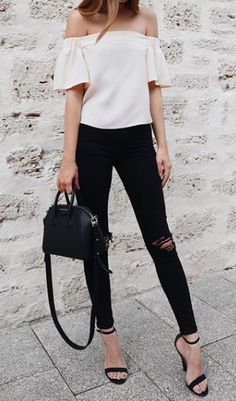 Ripped black skinny jeans, off the shoulder top and heeled sandals. Street style look.