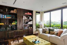 Decoração de apartamento com obras de arte. Sofá branco, luz natural, banquinho de madeira, estante de madeira com livros e adornos. #decoracao #decor #details #casadevalentina