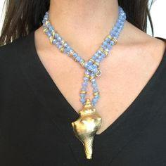 Collar largo de cristal de roca ahumada con caracola de latón bañada en oro mate. El collar va adornado con anillas también en latón y por la colocación de las