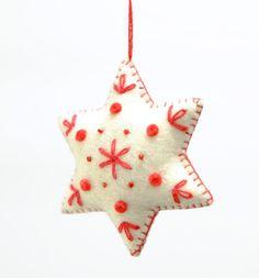 生成りのフェルト地を利用した星形のクリスマスツリー飾り。赤い糸の刺繍がアクセントに。ストラップとしてアクセサリーにも。  サイズ:8 cm x 8 cm x 3 cm カラー:ホワイト/ レッド