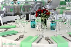 Mint green table setting for a tented wedding with lots of mason jars